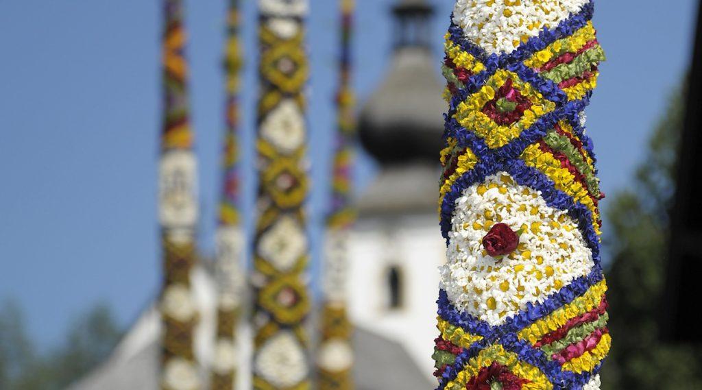 "Le tradizionali ""Prangstangen"": pali decorati con ghirlande di fiori veri"