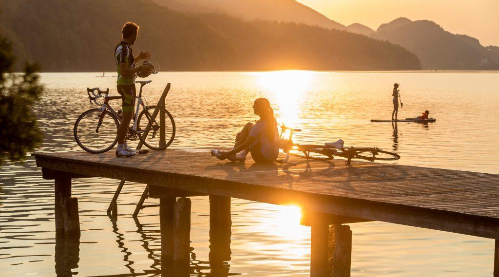 Twee wielrenners in de avond aan de oever van een bergmeer