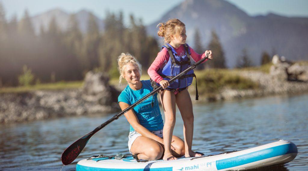 Een moeder en kinder op een surfplank