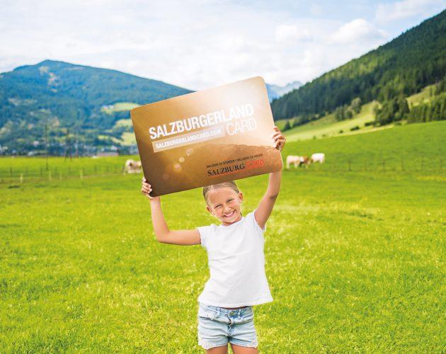 Een meisje houdt de SalzburgerLand Card omhoog