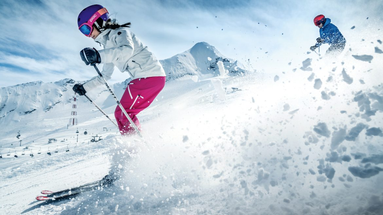 Een skiër stuift de sneeuw op