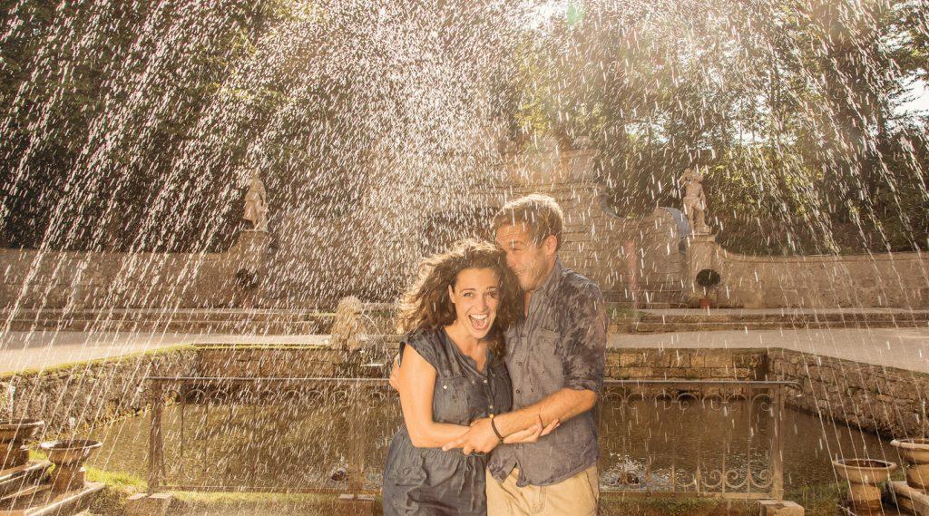 Een paar lacht bij de Wasserspiele terwijl fonteinen water spuiten
