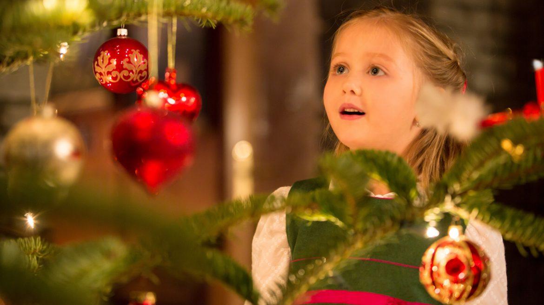 Een meisje bewondert een kerstboom
