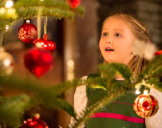 Dziewczynka podziwiająca choinkowe świecidełka